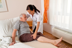 caregiver helping an elderly man in the bed